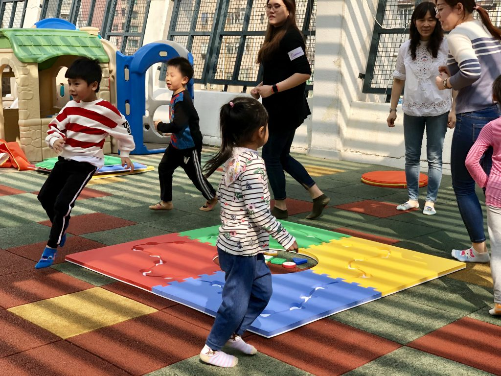 children are dancing around the mats