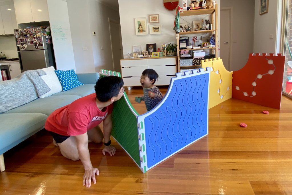 Father and son are playing Reach & Match in vertical configurations.