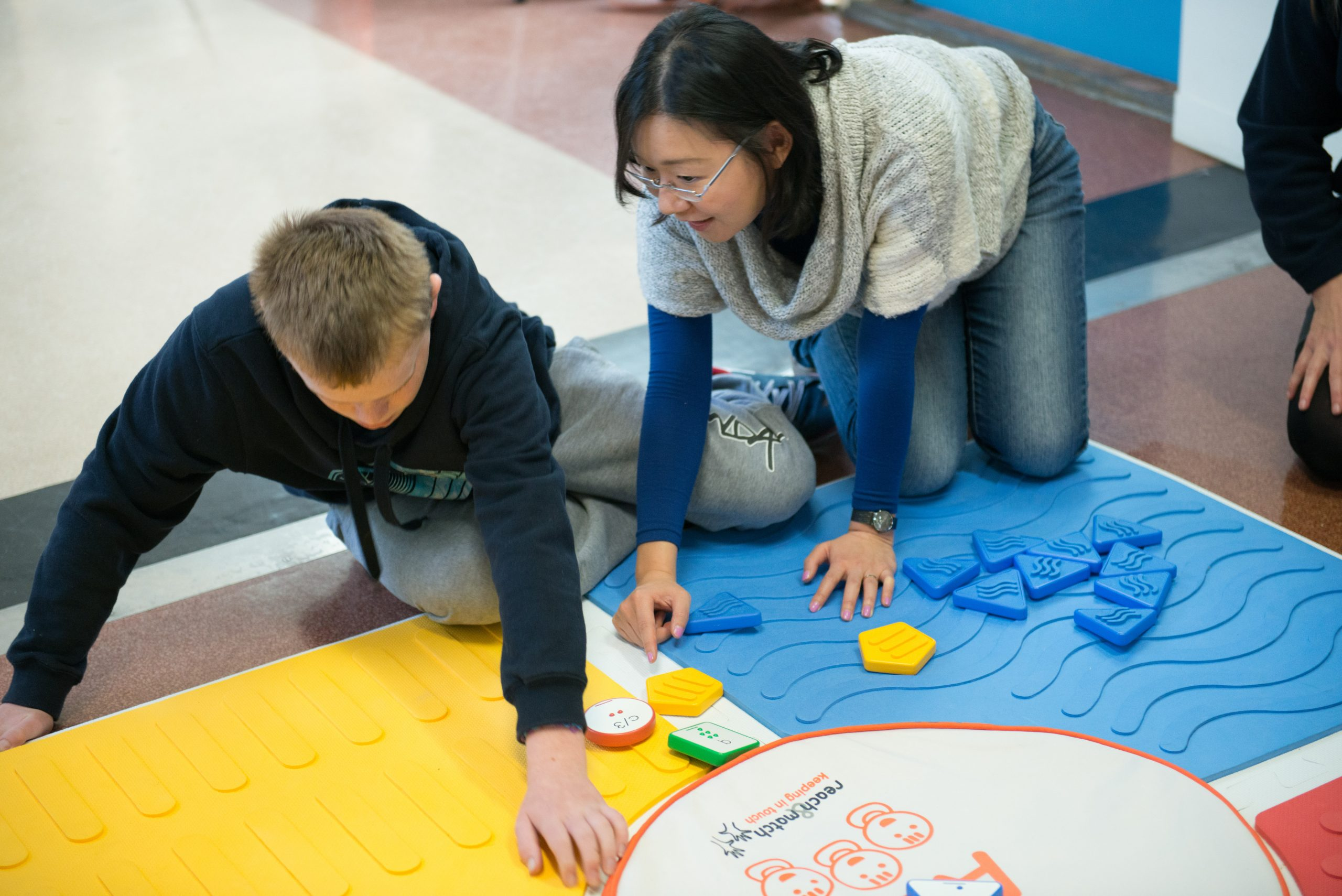 mandy lau teaches a blind student how to play reach and match