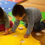 a little girl and a little boy are playing on the path side of Reach & Match mats. There are circle, triangle, square and pentagon tiles that can be put into the corresponding mats.