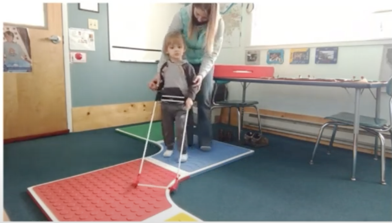 an O&M specialist worked with a preschool student to utilise his belt cane to walk on the path created by the Reach & Match mats